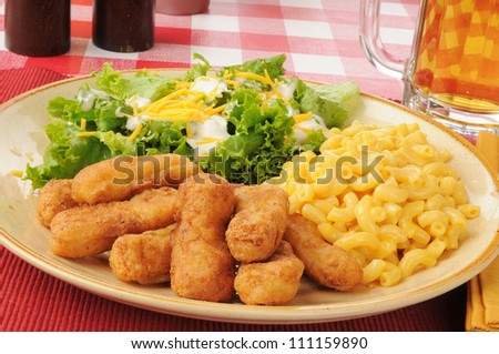 Battered chicken strips with macaroni and cheese and beer - stock photo