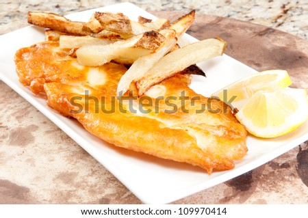 battered fish and chips with lemon wedges - stock photo