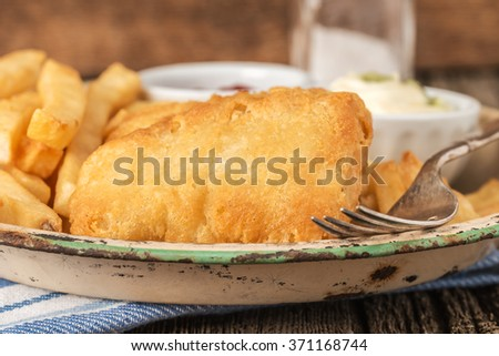 Battered fried haddock photographed closeup with a selective shallow depth of field. - stock photo