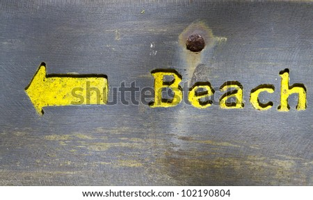 Battered old wooden sign pointing to the beach - stock photo