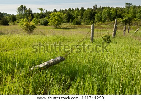 Battered Wire Fence in a Countryside - stock photo