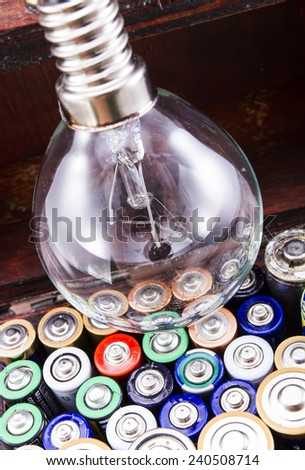 Batteries energy for an idea concept shot. Opened treasure chest with batteries and and a bulb lamp inside isolated on white/Batteries energy for an idea - stock photo