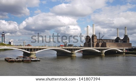 Battersea Power Station with the Grosvenor rail bridge in the foreground. It ceased generating electricity for London in 1983, but is still a well-known landmark. - stock photo