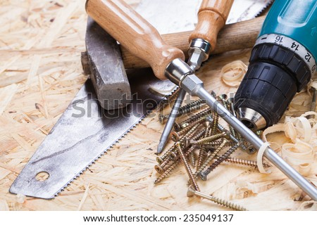 Battery-operated portable hand drill with timber, screwdrivers and screws surrounded by fresh wood shavings in a carpentry, joinery, DIY or construction concept