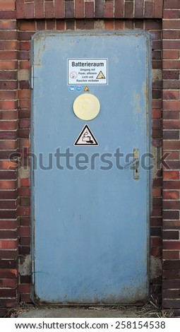Battery room with with warning sign and various symbols. The text means: Battery room - Fire, open flame, and smoking are forbidden. - stock photo