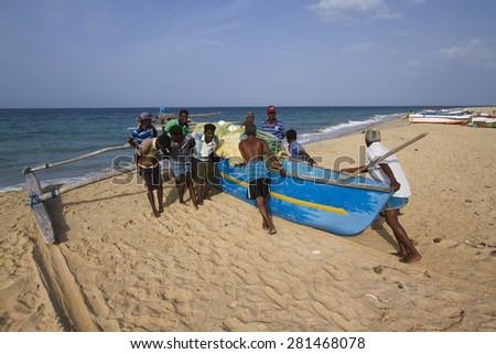 Batticaloa, Sri Lanka- June 24, 2014: Fishermen pushing dugout canoe in Batticaloa, Sri Lanka. They belong to tamil people ethnicity - stock photo