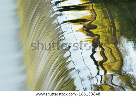 Battle Creek River cascade captured with motion blur and with abstract reflections of trees and sky in calm water, Michigan, USA  - stock photo
