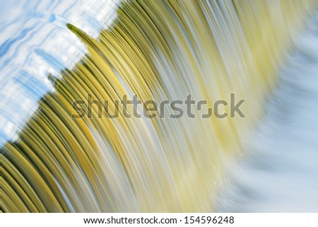 Battle Creek River cascade captured with motion blur and with reflections of sky in calm water, Michigan, USA - stock photo