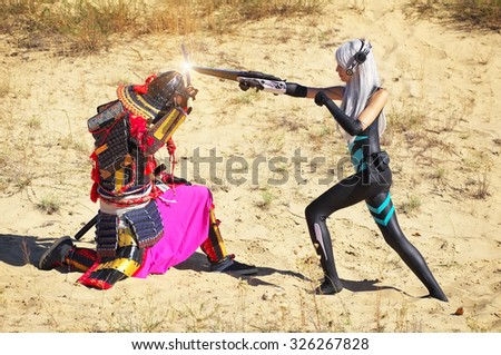 Battle of two characters: a man in samurai costume with sword and girl from the future with blade. Original cosplay. - stock photo