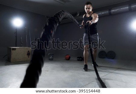 Battle ropes exercise in the garage - stock photo