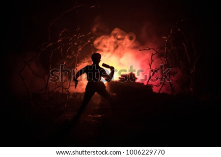 Battle scene. Soldier with grenade and blurred tank on background. Forest at night, mystical landscape surreal lights with creepy man. War battlefield