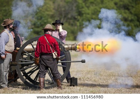 BATTLEFIELD, MO - AUG 11: Soldiers fire a cannon at Wilson's Creek National Battlefield Park during a reenactment on August 11, 2012 in Battlefield, MO. - stock photo
