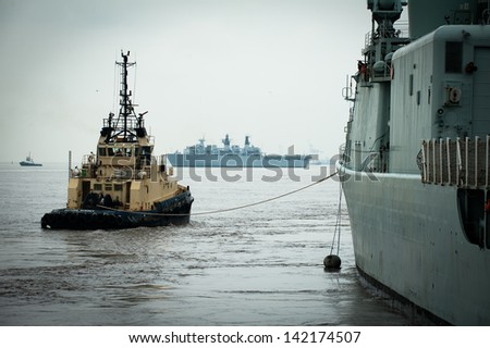 Battleships docking with a tug in Liverpool
