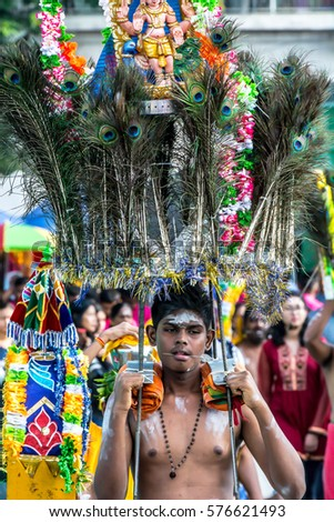 BATU CAVES, MALAYSIA - 9TH FEBRUARY 2017: Hindu devotees and his kavadi in a procession to the Batu Caves temple on Thaipusam day, a day of thanksgiving and devotion.