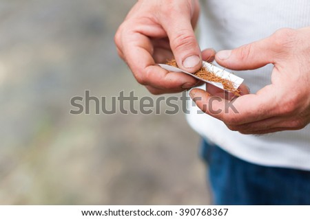 BATUMI - JULY 8: man makes a handmade cigarette in paper with brown tobacco at july 8, 2011. Smoking is a national tradition in Georgia and almost every person in this country smokes.
