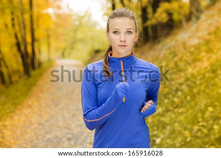 Bautiful running woman jogging in autumn nature - stock photo