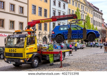 Bautzen, Germany - April 20th, 2014: The towing service picks up a car on their truck, watched by passersby, on April 20th, 2014, in Bautzen, Saxony, Germany.