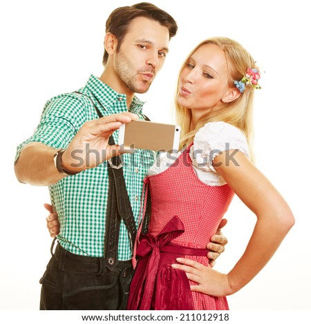 Bavarian couple taking selfie with duckface with a smartphone - stock photo