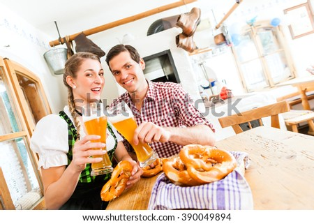 Bavarian couple wearing traditional dress, flirting and  drinking beer in restaurant - stock photo