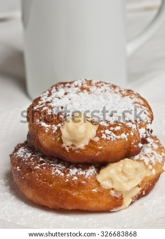 Bavarian Cream filled donut and white coffee cup - stock photo