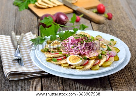 Bavarian dumpling salad, made of sliced bread dumplings, onion rings, radishes, spring onions, sliced eggs and gherkins, dressed with oil and apple vinegar and some herbs - stock photo