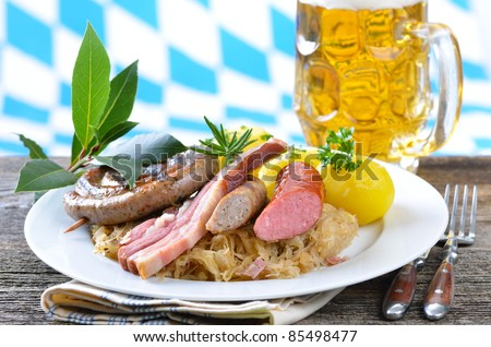 Bavarian fresh belly of pork and sausages on sauerkraut with potatoes - stock photo