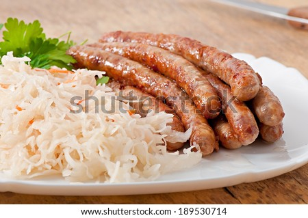 Bavarian fried sausages on sauerkraut - stock photo