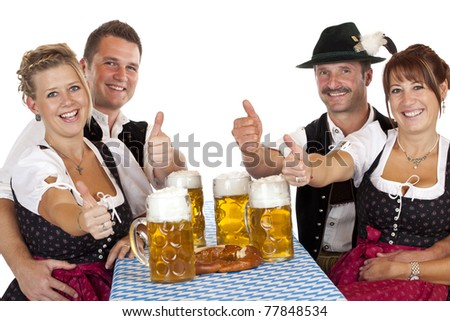 Bavarian girls and men with beer stein hold thumbs up. Isolated on white background. - stock photo