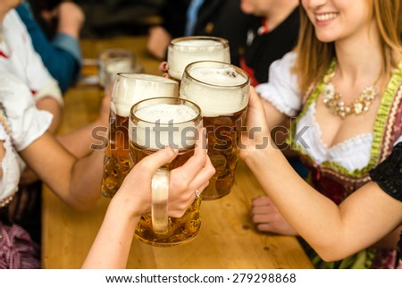 Bavarian girls in traditional Dirndl dresses are drinking beer and having fun at the Oktoberfest - stock photo