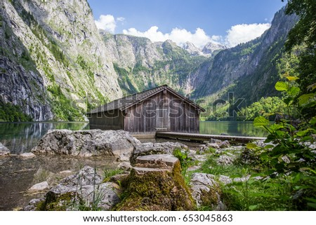 Bavarian landscape with wooden house and lake.