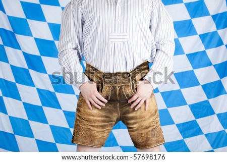 Bavarian man with brown Oktoberfest leather pants (Lederhose). In background is Bavarian flag visible. - stock photo