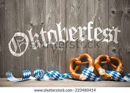 Bavarian pretzels with ribbon on wooden board. Background for Oktoberfest - stock photo