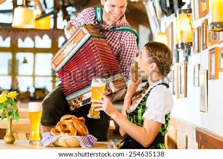 Bavarian restaurant with music, guests, wheat beer and pretzels - stock photo
