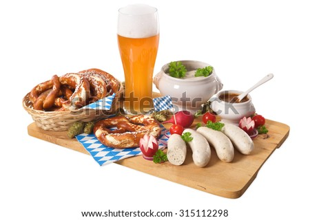 Bavarian veal sausage breakfast with sausages, soft pretzel, wheat beer and mild mustard on wooden board from Germany