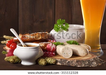Bavarian veal sausage breakfast with sausages, weissbier, soft pretzel and mild mustard on dark weathered wooden board from Germany