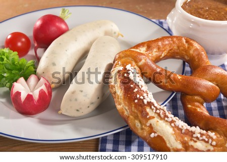 Bavarian veal sausage breakfast with two sausages, soft pretzels and mild mustard on wooden board from Germany - stock photo