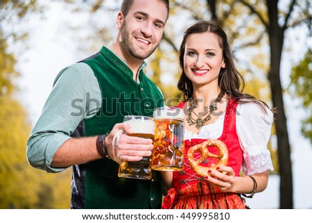 Bavarians in Tracht with Beer and Pretzel in autumn - stock photo
