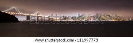 Bay Bridge and Lights San Francisco Skyline in the Fog at night - stock photo