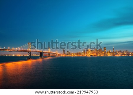 Bay Bridge and San Francisco downtown skyline at dusk - stock photo
