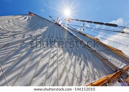 Bay City Tall Ship Celebration - Sun burst shining down along a large canvas sail under beautiful bright blue skies. Perfect sailing. - stock photo