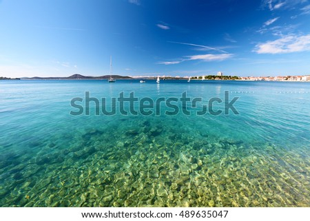 Bay of adriatic sea with town on horizon. Yacht and boat in water