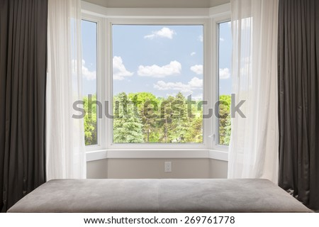 Bay window with drapes, curtains and view of trees under summer sky - stock photo