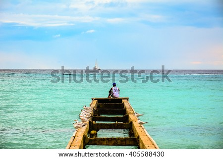 BAYAHIBE, DOMINICAN REPUBLIC - JANUARY 6, 2016 - A man sitting on top of a pier surrounded by seagulls observes the passage of a boat.
