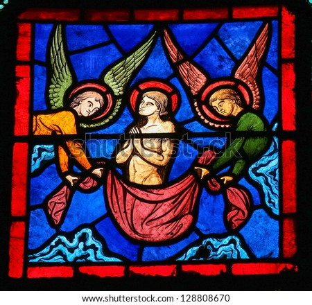 BAYEUX - FEBRUARY 12: Stained glass window depicting a saints ascent into Paradise, accompanied by two angels, in the cathedral of Bayeux, Normandy, France, on February 12, 2013. - stock photo