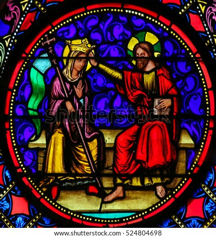 BAYEUX, FRANCE - FEBRUARY 12, 2013: Stained Glass window in the Cathedral of Bayeux, France, depicting Jesus and Mother Mary in Heaven.