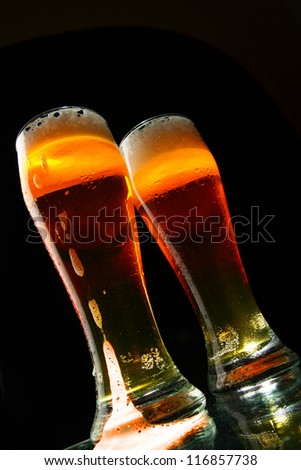 Bbeer with froth over black background - stock photo