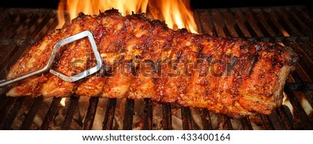 BBQ  Baby Back Or Spareribs Ribs Close-up On The Hot Flaming Grill - stock photo