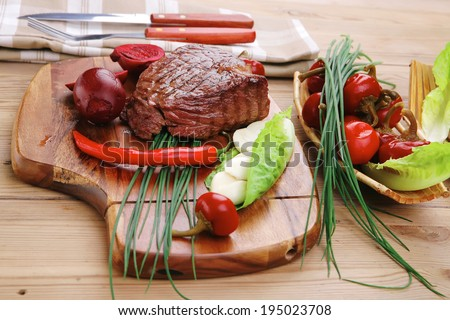 bbq : beef (pork) steak garnished with green staff and red chili hot pepper on wooden table with cutlery - stock photo