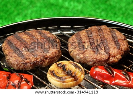 BBQ Burgers Cooked On Hot Charcoal Grill With Vegetables. Cookout Concept. Good Snack For Outdoor Party Or Picnic. Summer Backyard Lawn In The Background.