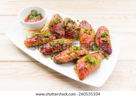 BBQ chicken wing on wood table - stock photo